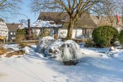 Vereister Dorfbrunnen am Haus des Gastes